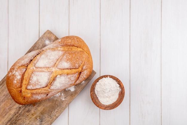 Bovenaanzicht van knapperig brood op snijplank en kom met bloem op houten achtergrond met kopie ruimte