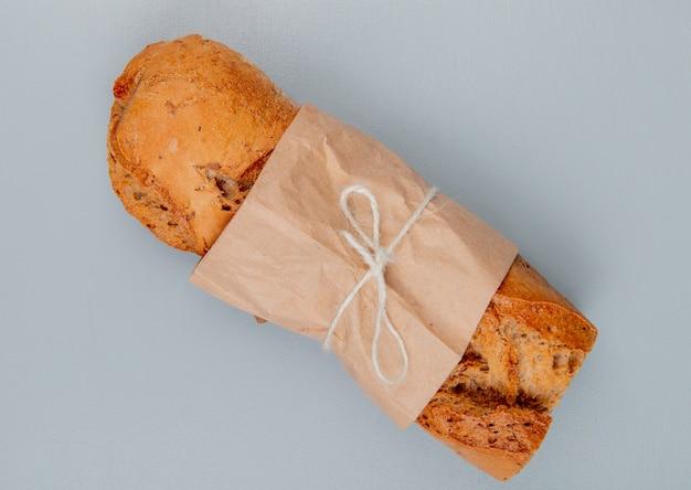 Bovenaanzicht van knapperig stokbrood verpakt in papier op blauwe achtergrond