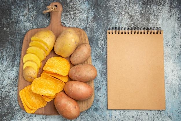 Bovenaanzicht van knapperige chips en ongekookte aardappelen op houten snijplank en notitieblok op grijze achtergrond