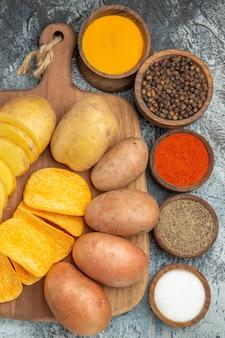 Bovenaanzicht van knapperige chips en ongekookte aardappelen op houten snijplank en verschillende kruiden op grijze tafel