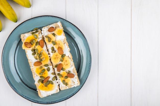 Bovenaanzicht van knapperige crackers met roomkaas, plakjes banaan, amandel en pompoenpitten op een bord op wit hout met kopie ruimte