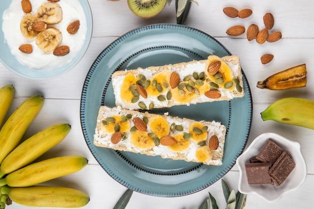 Bovenaanzicht van knapperige crackers met roomkaas, plakjes banaan, amandel en pompoenpitten op een plaat op wit hout