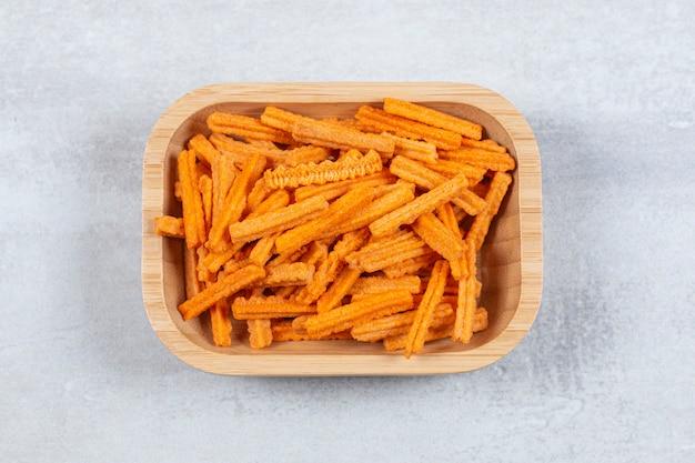 Bovenaanzicht van knapperige frietjes in houten kom.