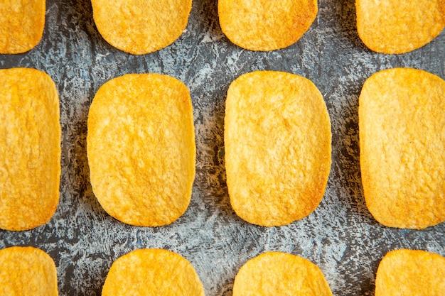 Bovenaanzicht van knapperige gebakken vijf chips opgesteld in rijen op grijze achtergrond
