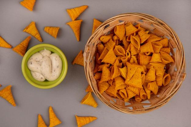 Bovenaanzicht van knapperige kegelvorm gebakken maïs snacks op een emmer met saus