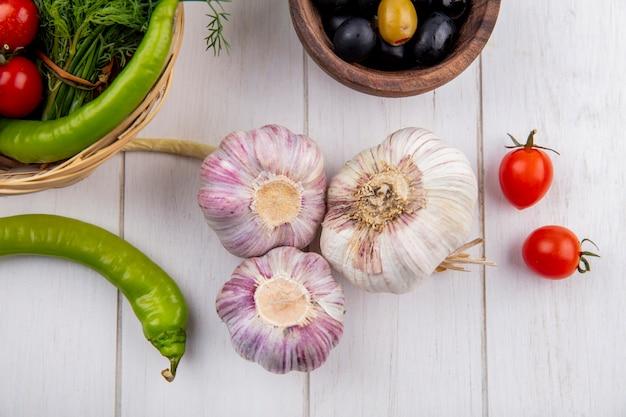 Bovenaanzicht van knoflook bollen met olijven, peper en cherry tomaten op houten oppervlak