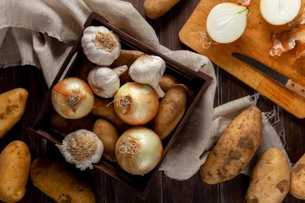 Bovenaanzicht van knoflook met uien en aardappelen