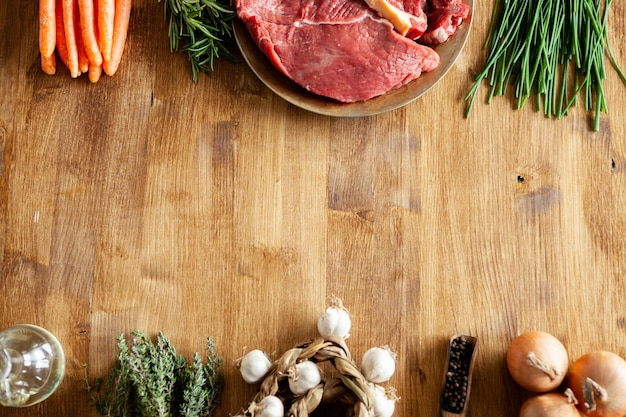 Bovenaanzicht van knoflook naast andere groenten en rood vlees in een vintage bord. kopieer beschikbare ruimte.