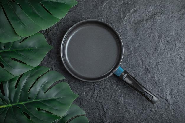 Bovenaanzicht van koekenpan op zwarte achtergrond met groene bladeren.