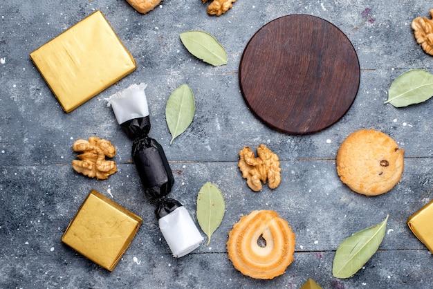 Bovenaanzicht van koekje en walnoten samen met chocoladetaart op grijs bureau, koekjeskoekje chocolade cacao