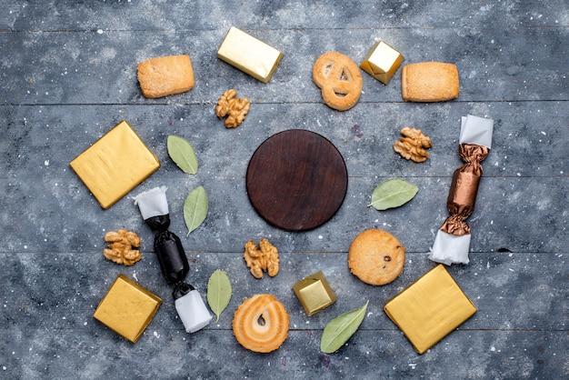 Bovenaanzicht van koekje en walnoten samen met chocoladetaart op grijs bureau, koekjeskoekje chocolade zoete suiker