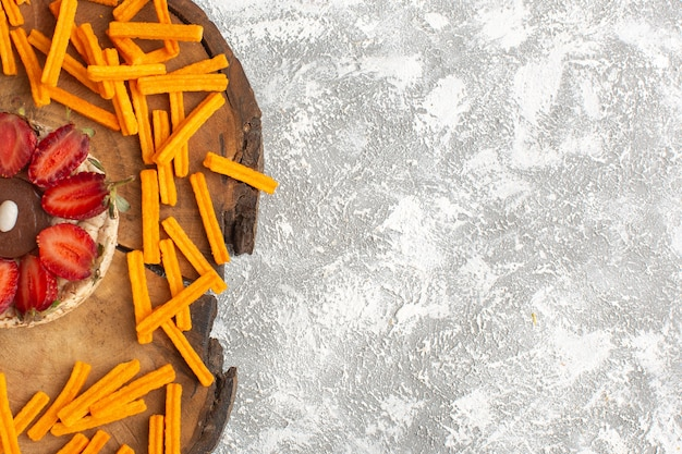 Bovenaanzicht van koekje met aardbeien met oranje beschuit op het houten bureau en lichte oppervlakte cake zoete dessert fruit suiker bakken