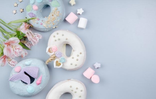 Bovenaanzicht van koekjes en snoepjes aan de linkerkant versierd met bloemen op paars met kopie ruimte