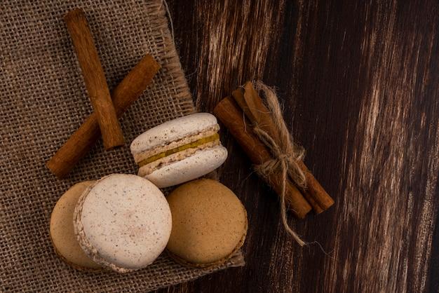 Bovenaanzicht van koekjes sandwiches en kaneel op zak en op houten achtergrond met kopie ruimte