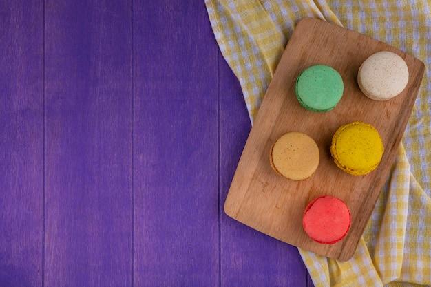 Bovenaanzicht van koekjes sandwiches op snijplank op geruite doek en paarse achtergrond met kopie ruimte