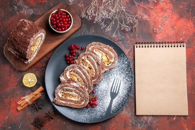 Bovenaanzicht van koekjesbroodjes met rood fruit op donkere ondergrond
