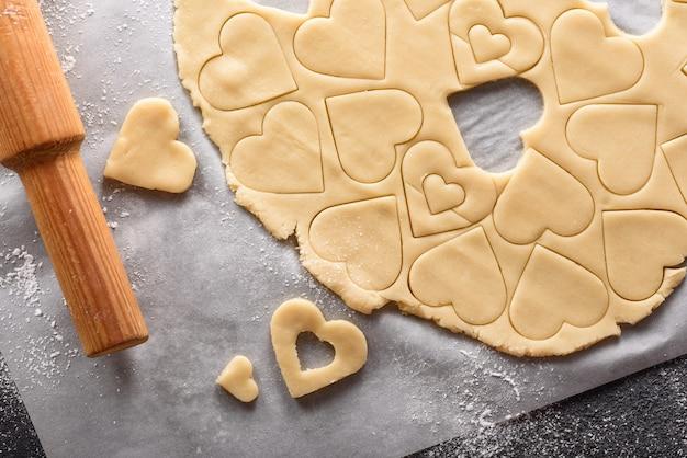 Bovenaanzicht van koekjesdeeg met uitgesneden vormen en deegroller op perkamentpapier, thuis bakken concept
