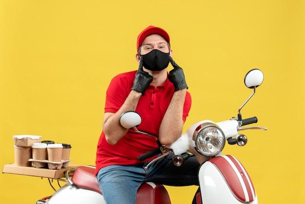 Bovenaanzicht van koerier man met rode blouse en hoed handschoenen in medisch masker leveren bestelling zittend op scooter te wijzen