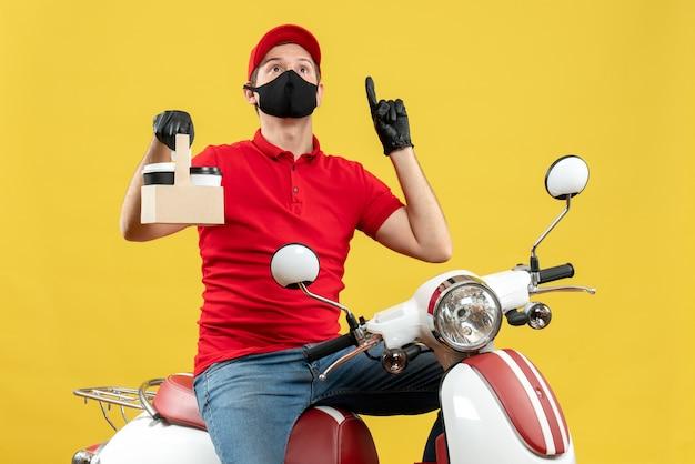 Bovenaanzicht van koerier man met rode blouse en hoed handschoenen in medische masker zittend op scooter houden bestellingen omhoog