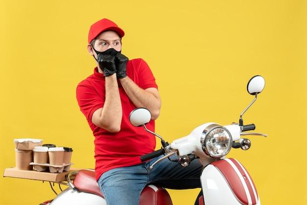 Bovenaanzicht van koerier man met rode blouse en muts handschoenen in medisch masker leveren bestelling zittend op scooter bang gevoel