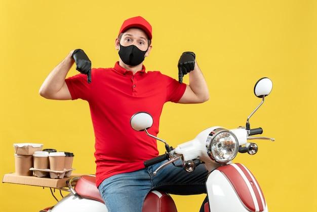 Bovenaanzicht van koerier man met rode blouse en muts handschoenen in medisch masker leveren bestelling zittend op scooter naar beneden