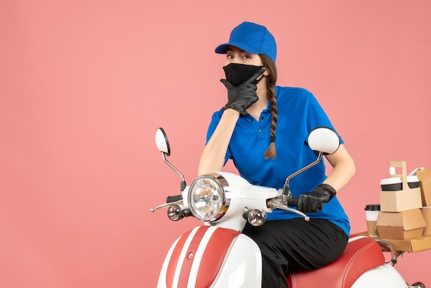 Bovenaanzicht van koeriersmeisje met een medisch masker en handschoenen die op een scooter zitten en bestellingen afleveren op een pastelkleurige perzikachtergrond