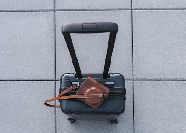 Bovenaanzicht van koffer en retro camera in lederen tas