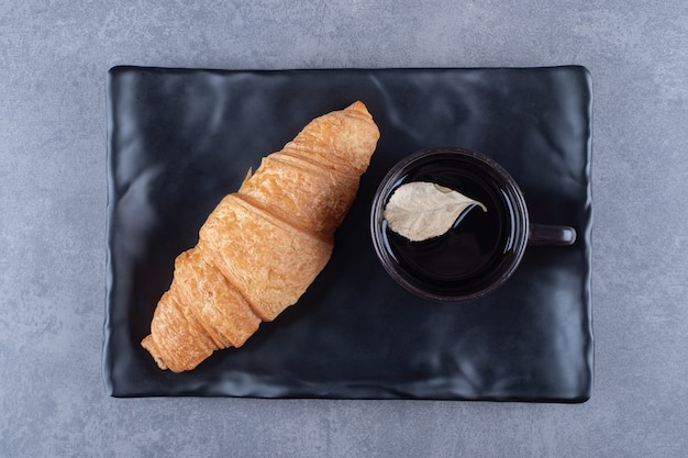Bovenaanzicht van koffie en croissant op zwarte plaat.