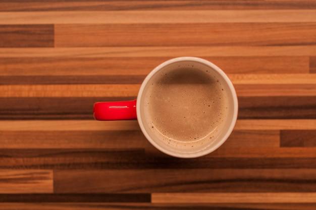 Bovenaanzicht van koffie in rode kop op houten vintage tafel. rode koffiekopje