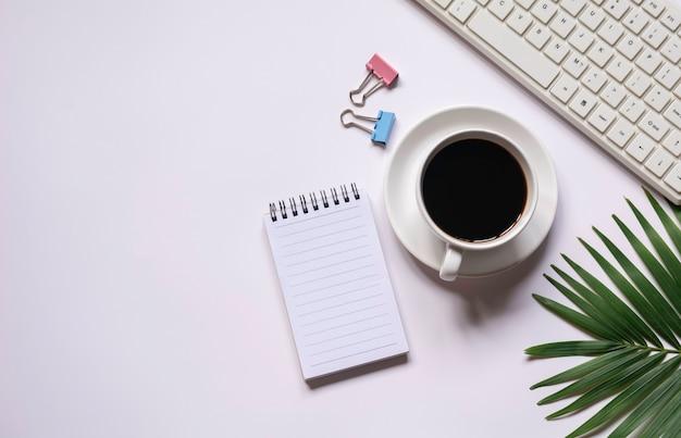 Bovenaanzicht van koffie met andere benodigdheden en toetsenbord op witte achtergrond en kopieer ruimte voor tekst invoegen.