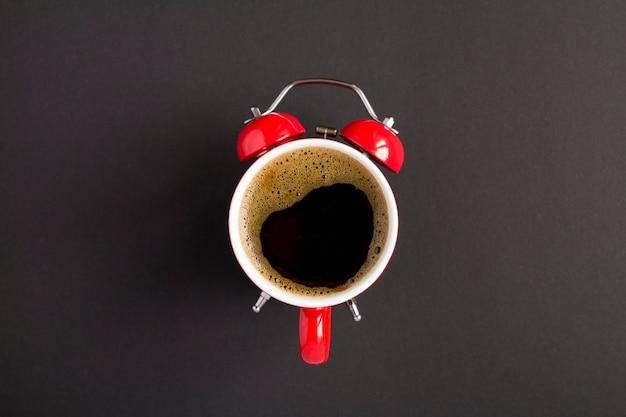 Bovenaanzicht van koffie op de wijzerplaat van de rode wekker in het midden van de donkere tafel