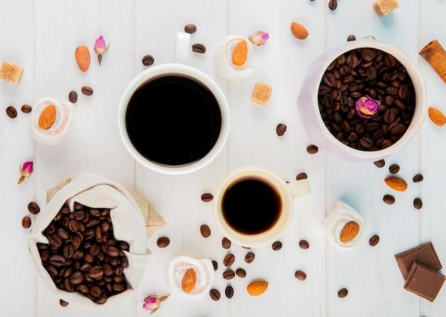 Bovenaanzicht van koffiebonen in een zak en kopjes koffie op witte achtergrond
