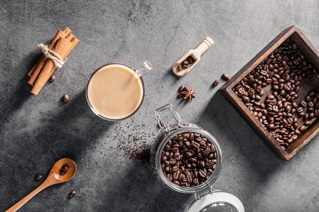 Bovenaanzicht van koffiekopje met bonen en kaneelstokjes
