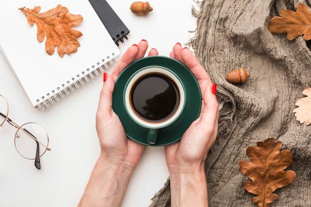 Bovenaanzicht van koffiekopje met herfstbladeren en notebooks