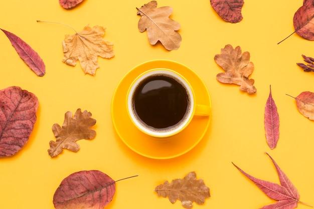 Bovenaanzicht van koffiekopje met herfstbladeren en plaat