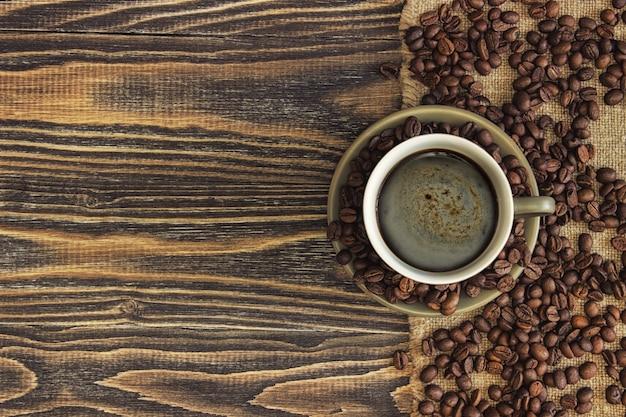 Bovenaanzicht van koffiekopje met koffiebonen en kopie ruimte