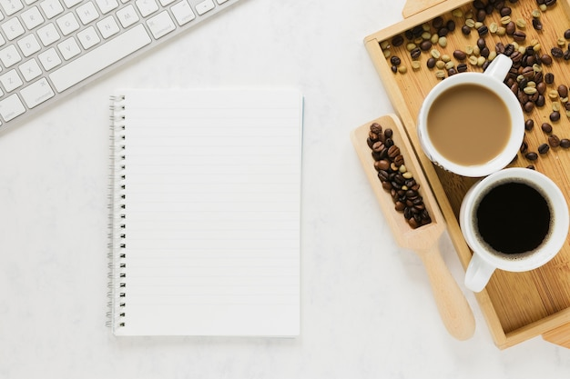 Bovenaanzicht van koffiekopjes met laptop