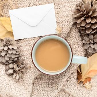 Bovenaanzicht van koffiemok met dennenappels en herfstbladeren