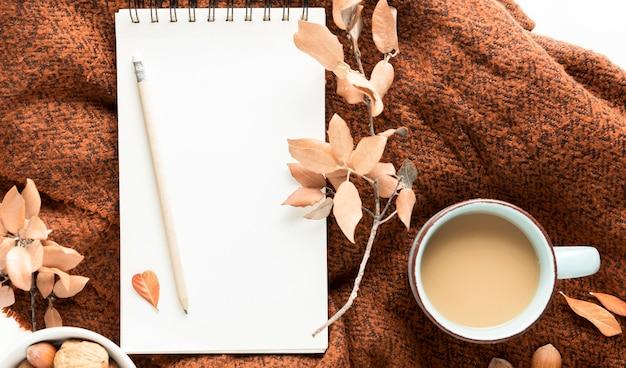 Bovenaanzicht van koffiemok met herfstbladeren en notebook