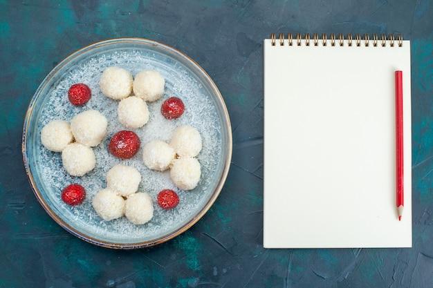 Bovenaanzicht van kokosnoot snoepjes en kladblok met potlood