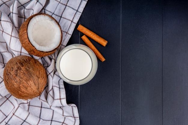Bovenaanzicht van kokosnoten met een glas melk met kaneelstokjes op gecontroleerd tafelkleed op zwart met kopie ruimte