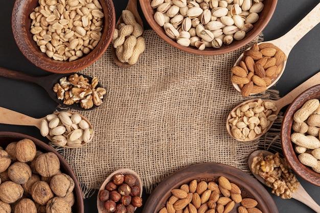 Bovenaanzicht van kom en lepel op jute met assortiment van noten