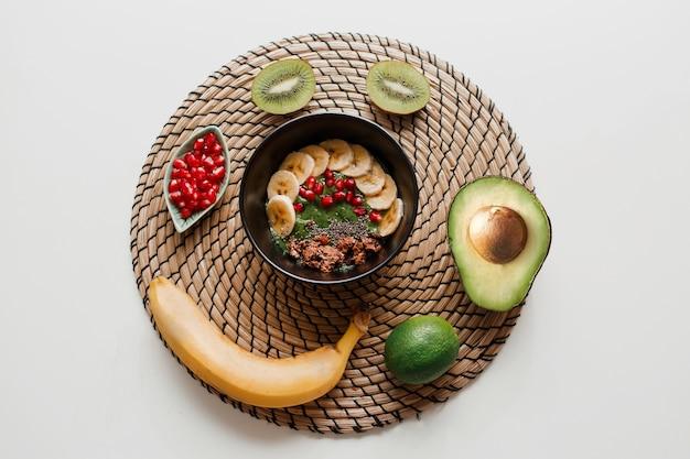 Bovenaanzicht van kom gegarneerd met avocado en spinazie, granaatappelpitjes en granola