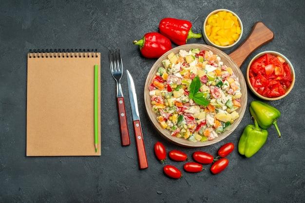 Bovenaanzicht van kom groentesalade met bestekgroenten en kladblok aan kant op donkergrijze tafel