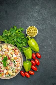 Bovenaanzicht van kom groentesalade met groen erop en groenten aan de zijkant op donkergroene achtergrond