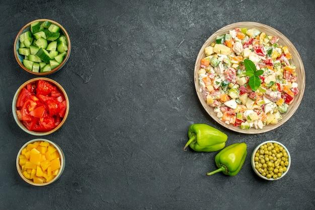 Bovenaanzicht van kom groentesalade met kommen groenten en paprika aan kant op donkergroene tafel