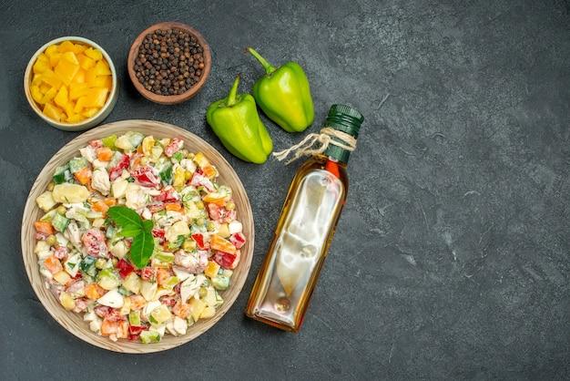 Bovenaanzicht van kom groentesalade met kommen groenten en peper olie fles en paprika aan kant op donkere achtergrond