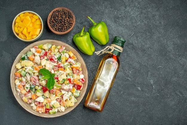 Bovenaanzicht van kom groentesalade met kommen groenten en peper olie fles en paprika aan kant op grijze achtergrond