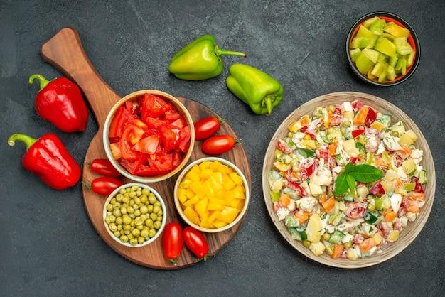 Bovenaanzicht van kom groentesalade met plaat staan van groenten aan kant op donkergrijze achtergrond