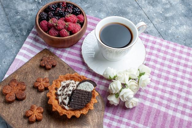 Bovenaanzicht van kom met bessen vers en rijp fruit met koekjes en koffie op grijs bureau, bessenfruit vers zacht bos